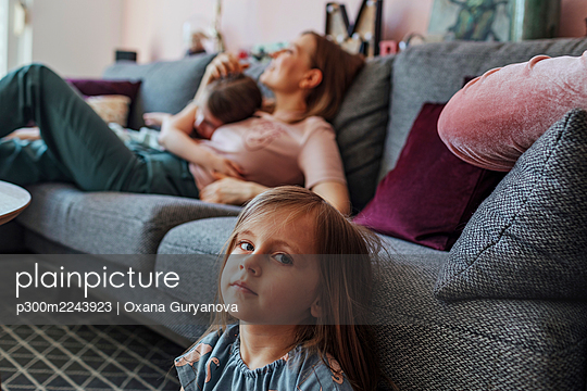 Mother with elder daughter while sister sitting below couch in living room - p300m2243923 by Oxana Guryanova