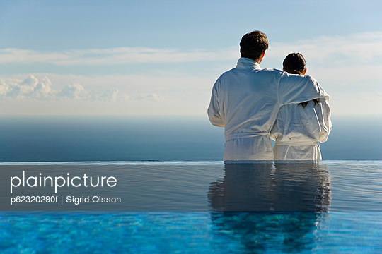 Couple standing at edge of infinity pool, looking at view