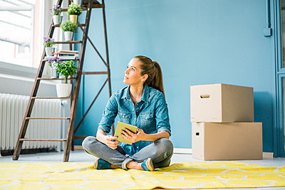 Woman sitting on floor of her new apartment, using digital tablet - p300m1568293 by Robijn Page