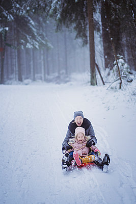 Portrait of mature woman sledging together with her daughter - p300m2144626 von Petra Silie