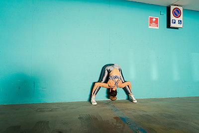 Woman practising yoga in parking lot - p429m2019432 by Ingolf Hatz