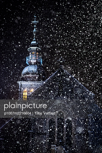 France, Le Grand Bornand, Illuminated Church with bell tower at night with snowflakes - p1007m2216604 by Tilby Vattard