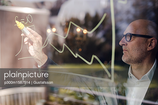 senior businessman brainstorming, drawing formulas on window pane - p300m1587514 von Gustafsson