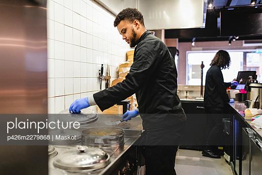 Male chef preparing dumplings in kitchen at restaurant - p426m2279868 by Maskot