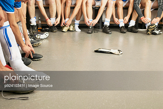 Football team tying laces - p92410341f by Image Source