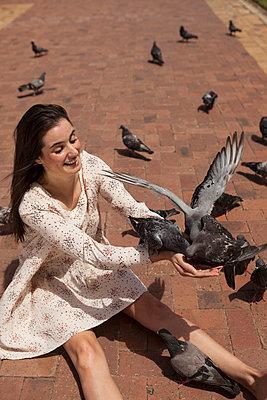 Frau füttert viele Tauben - p045m1355239 von Jasmin Sander