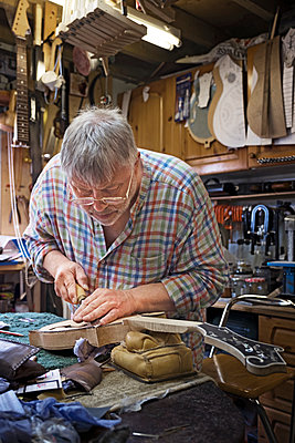Craftsman shaping guitar at workbench in workshop - p1166m1163578 by Cavan Images