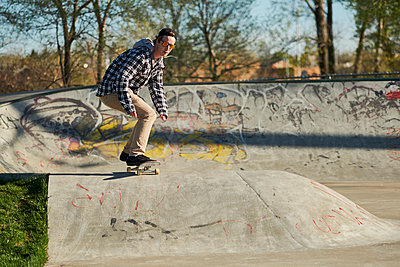 Male skateboard enthusiast rolling around concrete ramp in skatepark - p1362m1553695 by Charles Knox