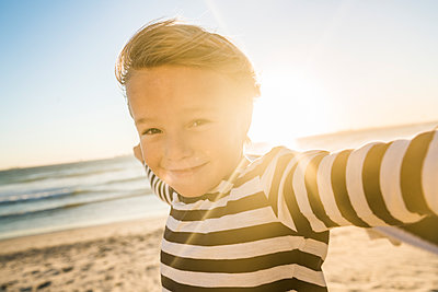 Portrait of smiling boy with a towel on the beach at sunset - p300m2167538 by Floco Images