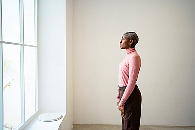 Woman looking through window while standing by wall at home - p300m2256539 by Rafa Cortés