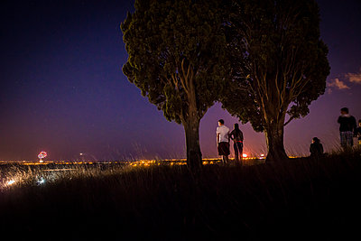 People looking at fireworks in the distance - p829m1110836 by Régis Domergue