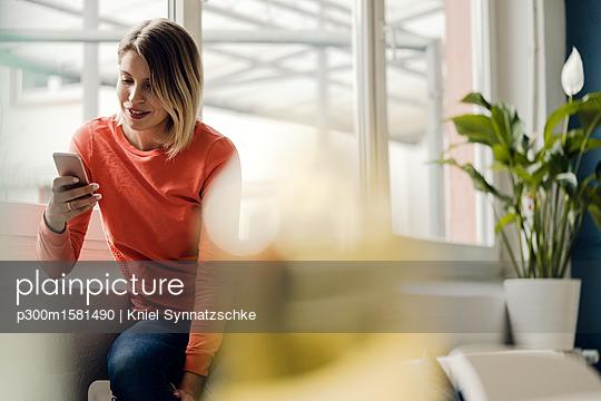 Woman using smartphone at home - p300m1581490 von Kniel Synnatzschke
