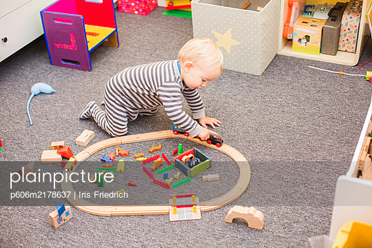 Little boy in romper playing with wooden railway - p606m2178637 by Iris Friedrich