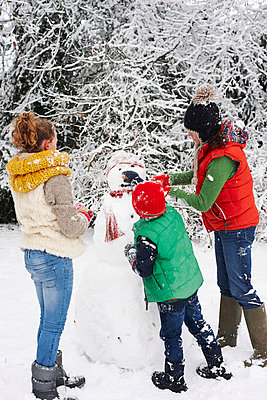Mother and children making snowman outdoors - p1023m806016f by Paul Viant