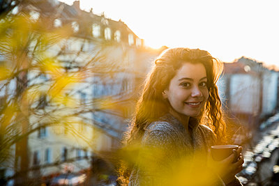 Portrait of laughing teenage girl with coffee mug on balcony at twilight - p300m1567976 by Jo Kirchherr