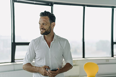 Portrait of confident mature businessman with cell phone in empty office - p300m2155418 by Kniel Synnatzschke