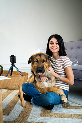 Smiling young woman with dog sitting on her lap in living room - p300m2266112 by Giorgio Fochesato