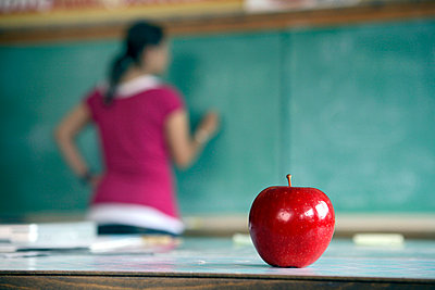 Teacher writing on chalkboard, apple in foreground - p3721902 by James Godman