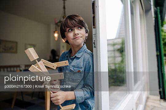 Little boy standing by window, holding self-made toy robot - p300m2167300 by Kniel Synnatzschke