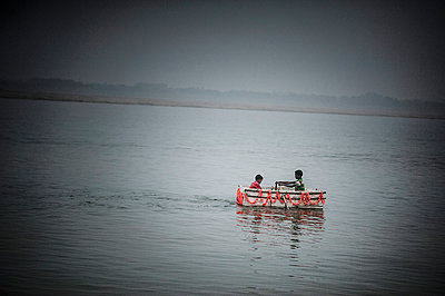Two children in a small boat - p1007m1144321 by Tilby Vattard