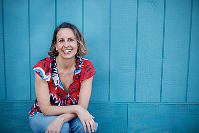 Portrait of happy woman sitting against blue wooden wall - p1166m2067927 by Cavan Images