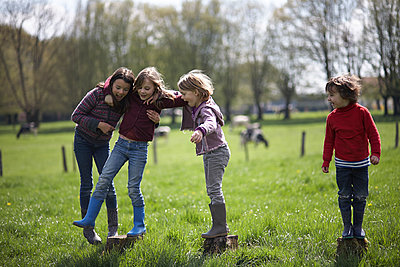 Four kids playing - p1430m1503587 by Charlotte Bresson