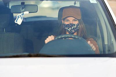 Young woman wearing face mask driving car in city - p300m2221164 by Kiko Jimenez