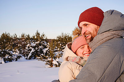 Father hugging smiling daughter in snow during winter - p300m2265136 by Ekaterina Yakunina