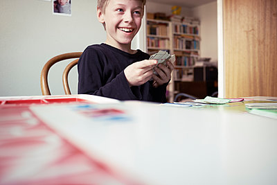 Smiling boy playing cards - p312m1187819 by Dan Lepp