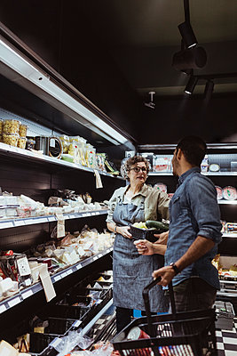 Female store owner talking with male customer at delicatessen shop - p426m2270716 by Maskot