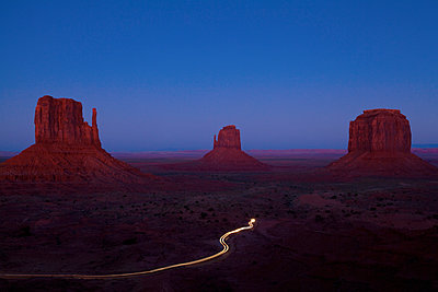 Long exposure of car driving past butte rock formations in desert landscape, Monument Valley Tribal Park, Utah, United States - p555m1415827 by Camilo Morales