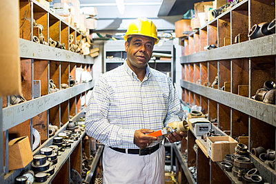 Portrait of man in plumbing stockroom with products - p924m821551f by Chad Springer