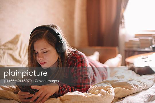 Teenage girl using smart phone while listening music on headphones - p1166m2113070 by Cavan Images
