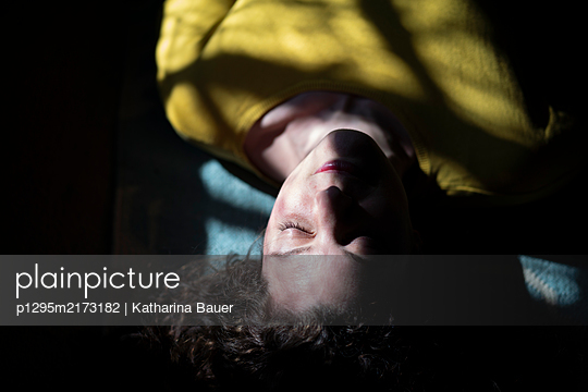 Woman in selfquaratine lying on carpet - p1295m2173182 by Katharina Bauer