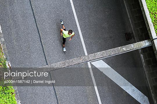 Top view of man running on a street - p300m1587142 von Daniel Ingold