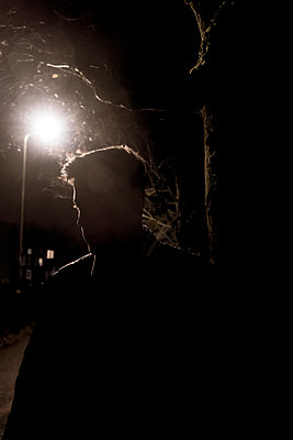 Silhouette of a young man walking in the dark - p1057m2045499 by Stephen Shepherd