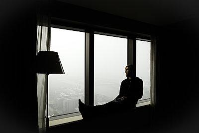 Mann auf Fensterbank blickt auf die Großstadt - p795m2044786 von Janklein