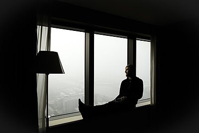 Man on windowsill watches the big city's skyline - p795m2044786 by Janklein