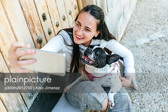 Young woman using smartphone, taking a selfie with her dog - p300m2012700 von Kiko Jimenez