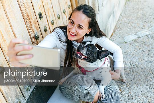 Young woman using smartphone, taking a selfie with her dog - p300m2012700 von Kiko Jimenez