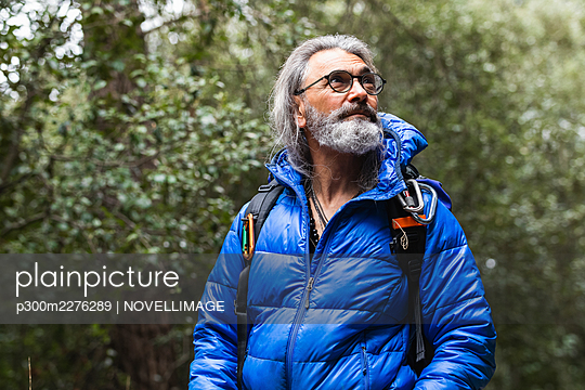 Senior man with gray hair looking away in forest - p300m2276289 by NOVELLIMAGE