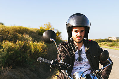young man riding his black motorcycle on the road with his helmet on - p1166m2137373 by Cavan Images