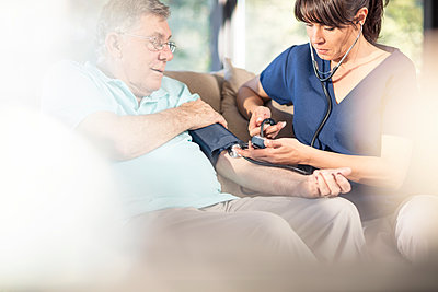 Nurse taking blood pressure of senior patient at home - p300m1537586 by zerocreatives