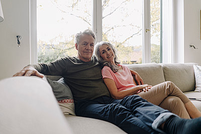 Portrait of senior couple relaxing on couch at home - p300m2156235 by Gustafsson