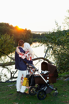 Parents with pram at lake - p312m2237426 by Pernille Tofte