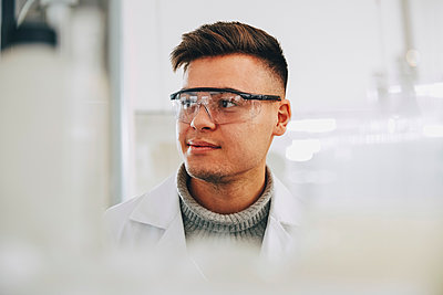 Confident young chemistry student wearing eyewear looking away in laboratory - p426m1570026 by Maskot