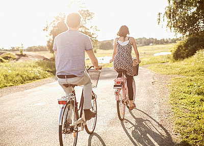Rear view of young friends riding bicycles on country road - p426m858128f by Maskot