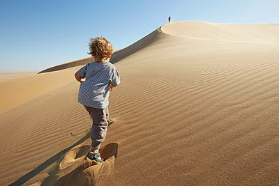 Boy walking on sand, Dune 7, Namib-Naukluft National Park, Africa - p429m1029681 by Stephen Lux