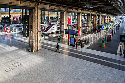 A man alone in a railway station - p940m2179788 by Bénédite Topuz