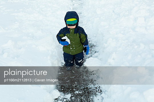 Cold toddler boy walks in shoveled pathway holding a snowball in arm - p1166m2112813 by Cavan Images
